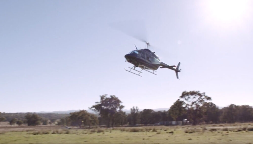 A helicopter lands in a paddock