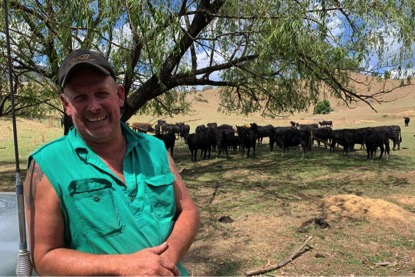Michael Ryan poses in front of his herd of cows