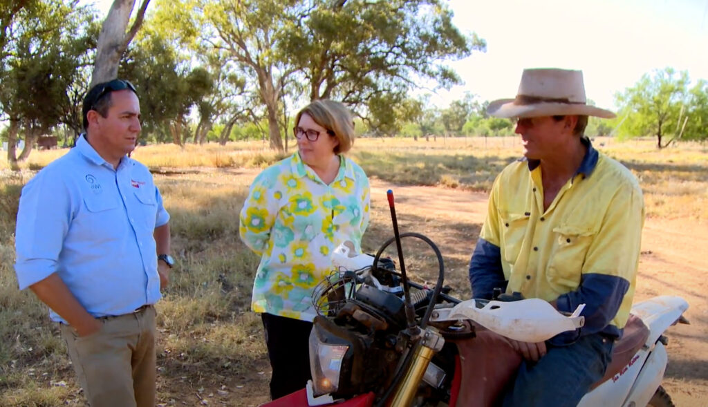 Three people in discussion in a rural setting